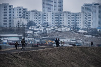 People are seen in a regional city in North Korea, with high-rise apartment buildings in the background, in December 2016. (Photo courtesy of Ari Hatsuzawa)