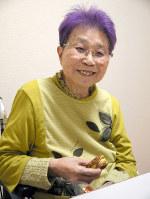 好物のお菓子を食べながら、笑顔を見せる岸君江さん=広島県三次市で2018年4月19日、田中博子撮影