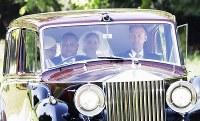 ホテルから母親とともに車で結婚式に向かうメーガン・マークルさん(中央)=ロンドン郊外の聖ジョージ礼拝堂で19日、AP