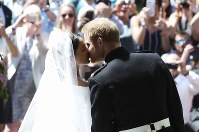 結婚式を終え、教会から姿を現しキスをするヘンリー王子とメーガン・マークルさん=ロンドン郊外の聖ジョージ礼拝堂で19日、AP