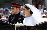 結婚式を終え、聖ジョージ礼拝堂を後にしてパレードに向かうヘンリー王子とメーガン・マークルさん=ロンドン郊外のウィンザー城でで19日、AP