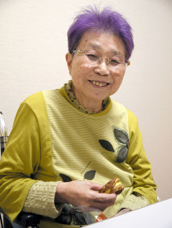Kimie Kishi smiles while eating her favorite sweets, in Miyoshi, Hiroshima Prefecture, on April 19, 2018. (Mainichi)