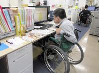 社会福祉法人「共生シンフォニー」で働くスタッフたち。手前の男性はパソコンで会計事務を処理していた=大津市で