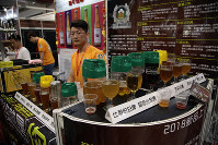 In this Wednesday, May 16, 2018, photo, a vendor waits for visitors at a beer booth at the 2018 Craft Beer of China Exhibition in Shanghai. Hundreds of craft beer enthusiasts, investors and brewers are attending an exhibition in Shanghai dedicated to expanding the palette of Chinese consumers and promoting sales of high-end brews. (AP Photo/Sam McNeil)