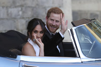 The newly married Duke and Duchess of Sussex, Meghan Markle and Prince Harry, leave Windsor Castle in a convertible car after their wedding in Windsor, England, to attend an evening reception at Frogmore House, hosted by the Prince of Wales, on Saturday, May 19, 2018. (Steve Parsons/pool photo via AP)