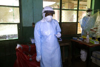 In this photo taken on Sunday, May 13, 2018, a health care worker wears virus protective gear at a treatment center in Bikoro Democratic Republic of Congo. (AP Photo/John Bompengo)