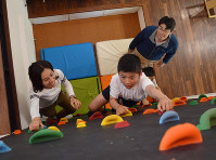 リビングのボルダリング壁に挑む子どもたちを見守る中村亮太さん(右)=水戸市で