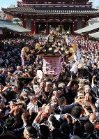 Participants carry a portable shrine belonging to Asakusa Jinja shrine through throngs of people for one of Tokyo's three great festivals, the