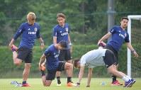 サッカー日本代表の合宿が始まり、練習で体をほぐす本田(左)、岡崎(右)ら=千葉県内で2018年5月21日、長谷川直亮撮影