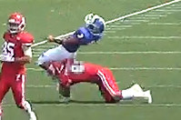 In this image taken from video and provided by Kwansei Gakuin University, a Kwansei Gakuin quarterback, center, is tackled from behind by a Nihon University player during an American football game on May 6, 2018 in Tokyo.