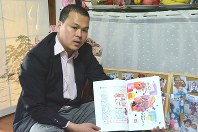 Le Anh Hao holds a booklet of the drawings and compositions that his slain 9-year-old daughter drew and wrote while attending elementary school, in Matsudo, Chiba Prefecture, on May 19, 2018. (Mainichi)