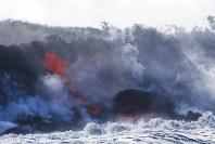 Lava flows into the ocean near Pahoa, Hawaii, on May 20, 2018. (AP Photo/Jae C. Hong)
