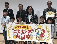 子どもたちと記念撮影に応じる又吉直樹さん(前列左から4人目)=東京都荒川区で