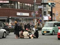 京都大学前の百万遍の交差点にこたつを持ち込み居座る若者ら=京都市左京区で2018年2月25日、通行人提供(画像の一部を加工しています)