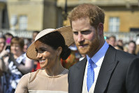 Meghan, the Duchess of Sussex walks with her husband, Prince Harry as they attend a garden party at Buckingham Palace in London, on May 22, 2018. (Dominic Lipinski/Pool Photo via AP)