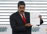 Venezuela's President Nicolas Maduro holds up a National Electoral Council, CNE, certificate declaring him the winner of the presidential election, during a ceremony at CNE headquarters in Caracas, Venezuela, on May 22, 2018. (AP Photo/Ariana Cubillos)