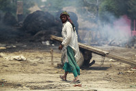 An Indian man walks near smoke rising from a residential area that was gutted from alleged fire from the Pakistan side of the border in the Jora farm village, in the Ranbir Singh Pura district of Jammu and Kashmir, India, on May 22, 2018. (AP Photo/Channi Anand)