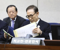 Former South Korean President Lee Myung-bak, right, appears for his first trial at the Seoul Central District Court in Seoul on May 23, 2018. (Chung Sung-Jun/Pool Photo via AP)