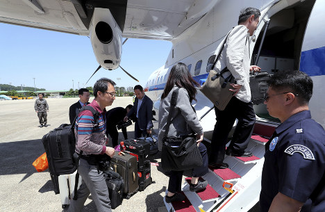 South Korean journalists board a plane to leave for North Korea, at Seoul Airport in Seongnam, South Korea, on May 23, 2018. (Yonhap via AP)