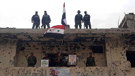 In this photo released by the Syrian official news agency SANA, Syrian military and police forces fly their national flags on a damaged building and hold a picture of Syrian President Bashar Assad, in the Hajar al-Aswad neighborhood, southern Damascus, Syria, on May 22, 2018. (SANA via AP)