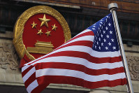 In this Nov. 9, 2017 file photo, an American flag is flown next to the Chinese national emblem during a welcome ceremony for visiting U.S. President Donald Trump outside the Great Hall of the People in Beijing. (AP Photo/Andy Wong)