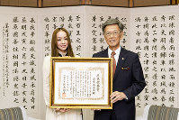 Pop singer Namie Amuro, left, who received an award from her home prefecture of Okinawa for inspiring the local population, holds a certificate of commendation with Gov. Takeshi Onaga at the prefectural government office on May 23, 2018.
