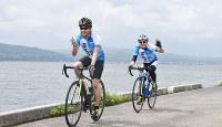 宍道湖をバックに笑顔を見せるサイクリストたち=松江市で、鈴木周撮影