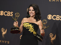 In this Sept. 17, 2017 file photo, Julia Louis-Dreyfus poses in the press room with her awards for outstanding lead actress in a comedy series and outstanding comedy series for