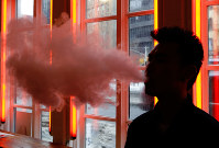 In this Feb. 20, 2014 file photo, a customer exhales vapor from an e-cigarette at a store in New York. (AP Photo/Frank Franklin II)