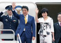 Japanese Prime Minister Shinzo Abe, left, and his wife Akie wave as they depart for Russia at Haneda Airport in Tokyo, on May 24, 2018. (Mainichi)