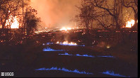 This photo from video from the U.S. Geological Survey shows blue burning flames of methane gas erupting through cracks on Kahukai Street in the Leilani Estates neighborhood of Pahoa on the island of Hawaii during the overnight hours of May 23, 2018. (U.S. Geological Survey via AP)