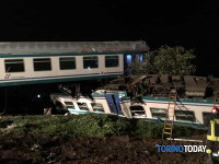 Firemen and rescue personnel work next to a train that plowed into a big-rig truck that was on the tracks, killing the train's engineer and injuring 16 passengers near Turin, northern Italy, early on May 24, 2018. (Torino Today via AP)