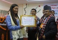 Nepalese woman climber Lhakpa Sherpa, left, receives an honorary certificate in Kathmandu, Nepal, on May 23, 2018. (AP Photo/Niranjan Shrestha)