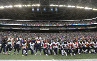 In this Oct. 29, 2017, file photo, Houston Texans players kneel and stand during the singing of the national anthem before an NFL football game against the Seattle Seahawks, in Seattle. (AP Photo/Elaine Thompson)