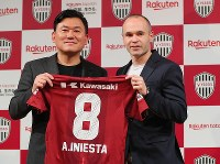 Former FC Barcelona player Andres Iniesta holds his new uniform with Rakuten Inc. President Koji Mikitani during a news conference announcing his move to Vissel Kobe, on May 24, 2018 in Tokyo. (Mainichi)