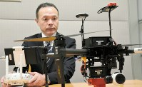Sompo Japan Nipponkoa Insurance Inc. chief technologist Yoshihito Takahashi is seen with a company drone in Tokyo's Shinjuku Ward in this recent photo. (Mainichi)