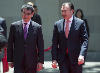 Japanese Foreign Minister Taro Kono, left, walks with Mexico's Secretary of Foreign Affairs Luis Videgaray during his welcoming ceremony in Mexico City, Thursday, May 24, 2018. (AP Photo/Eduardo Verdugo)