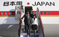 Japanese Prime Minister Shinzo Abe, foreground left, and his wife Akie, foreground right, exit the plane upon their arrival in St. Petersburg, Russia, on May 24, 2018. (Alexander Ryumin/TASS News Agency Pool Photo via AP)