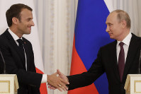 Russian President Vladimir Putin, right, and French President Emmanuel Macron, shake hands after their joint news conference following talks at the Konstantin palace with the statue of Peter the Great in the background, just outside St. Petersburg, Russia, on May 24, 2018. (AP Photo/Dmitri Lovetsky)