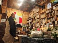 鈴木均さんの遺言で長野県内の八ケ岳山麓で営まれた葬儀で、お経をあげる高橋和尚。壁一面の本棚には、均さんの愛した書籍で埋め尽くされていた=2018年5月9日、萩尾信也撮影