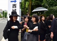 A group of women who traveled to Tokyo from Osaka on a Shinkansen bullet train to attend Hideki Saijo's funeral gather at Aoyama Funeral Hall in Minato Ward, Tokyo, on May 26, 2018. (Mainichi)