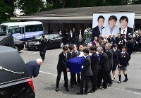 Singer Goro Noguchi, center left, and others carry the coffin of Hideki Saijo at Aoyama Funeral Hall in Minato Ward, Tokyo, on May 26, 2018. (Mainichi)