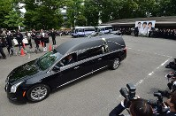 A car carrying the coffin of Hideki Saijo leaves Aoyama Funeral Hall in Minato Ward, Tokyo, on May 26, 2018. (Mainichi)