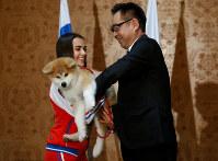 秋田犬を贈呈され笑顔のザギトワ選手=2018年5月26日、ロイター