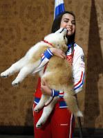 秋田犬を贈呈され笑顔のザギトワ選手=2018年5月26日、AP