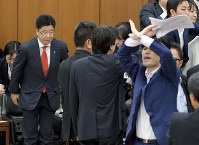 Health, Labor and Welfare Minister Katsunobu Kato, left, bows after the House of Representatives Committee on Health, Labor and Welfare approved the work-style reform bill amid protests from opposition parties on May 25, 2018. (Mainichi)