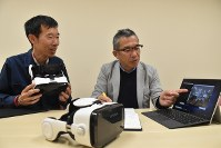 Satoshi Sakai, right, looks at a video taken with a 360-degree camera while Eiichi Miyazaki holds a virtual reality terminal for understanding how those with autism experience their surroundings, at Kagawa University, in Takamatsu, on April 25, 2018. (Mainichi)