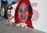 A woman places flowers by a mural showing Savita Halappanavar, a 31-year-old Indian dentist who had sought and been denied an abortion before she died after a miscarriage in a Galway hospital, with the word YES over it, in Dublin, Ireland, on the day of a referendum on the 8th amendment of the constitution. (Niall Carson/PA via AP)