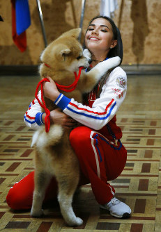 Russian Women's Olympic Figure Skating Gold medalist Alina Zagitova plays with an Akita Inu puppy named Masaru presented by Japanese Prime Minister Shinzo Abe, in Moscow, Russia, Saturday, May 26, 2018. (AP Photo/Alexander Zemlianichenko, Pool)