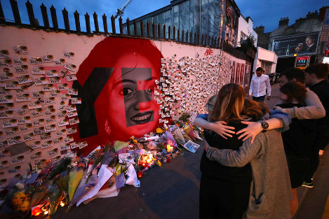 Candle and flowers are placed in front of a mural of Savita Halappanavar in Dublin, Ireland, Saturday, May 26, 2018, as Ireland has voted to repeal the 8th Amendment of the Irish Constitution which prohibits abortions unless a mother's life is in danger. (Niall Carson/PA via AP)